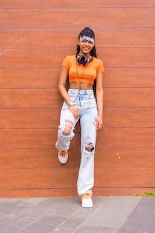 Lifestyle met een jonge trapdanseres in de stad. zwart-rasmeisje van afrikaanse etnische groep met oranje t-shirt en cowboybroek