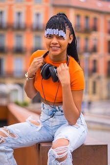 Lifestyle met een jonge trapdanseres met vlechten. black-race meisje pose met afrikaanse etnische groep met oranje shirt en cowboy broek zitten. met oranje huizenachtergrond