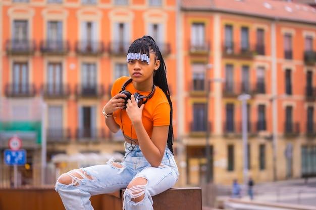 Lifestyle met een jonge trapdanseres met vlechten. black-race meisje van afrikaanse etnische groep met oranje shirt en cowboy broek zitten. met oranje huizenachtergrond