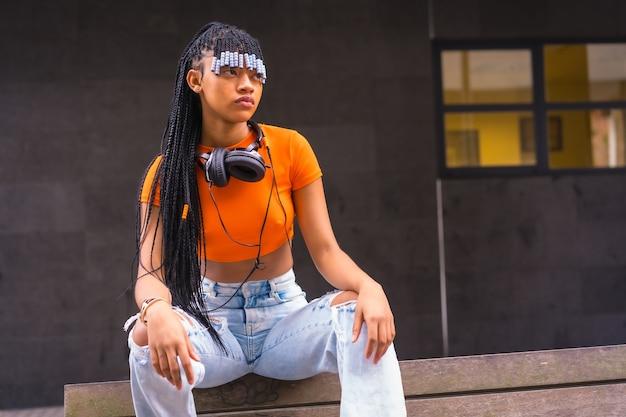 Lifestyle met een jonge trapdanseres met vlechten in de stad. zwart-rasmeisje van afrikaanse etnische groep met oranje t-shirt en cowboybroek