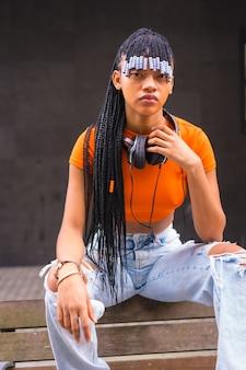 Lifestyle met een jonge trapdanseres met vlechten in de stad. zwarte racemeisje afrikaanse etniciteit met oranje t-shirt en cowboybroek, verticale foto