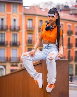 Lifestyle met een jonge trapdanseres met vlechten. zwart meisje van afrikaanse etnische groep met oranje t-shirt en cowboybroek. met huizen
