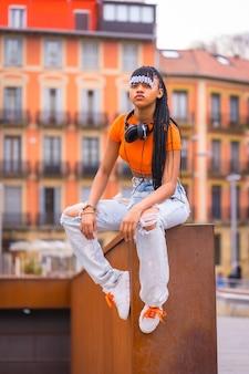 Lifestyle met een jonge trapdanseres met vlechten. zwart meisje van afrikaanse etnische groep met oranje t-shirt en cowboybroek. met oranje huizenachtergrond