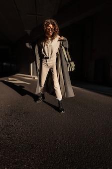 Lifestyle mode gelukkig mooi meisje met krullend haar in trendy stedelijke kleding look met een jas, een trui en een stijlvolle handtas wandelingen in de stad op het asfalt met licht en schaduw