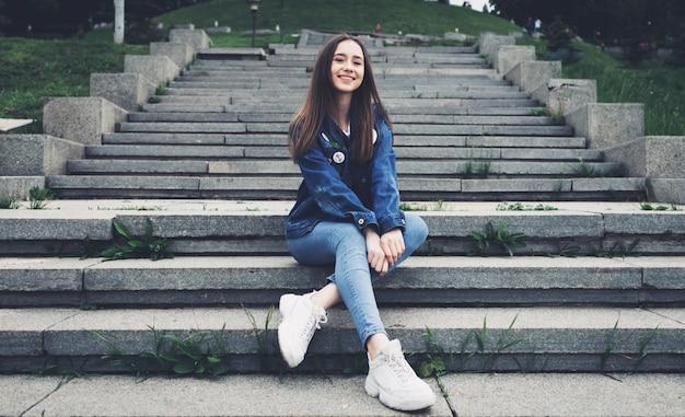 Lifestyle mode stijlvolle tiener zit op stappen in het stadspark in denim kleding