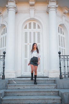 Lifestyle, modieuze pose van een jonge brunette met een zwarte leren rok en een shirt op de trappen van een wit huis