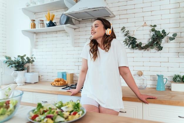 Lifestyle-momenten van een jonge vrouw thuis. vrouw bereidt een salade in de keuken