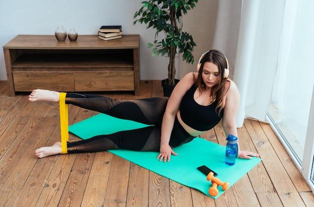 Lifestyle-momenten van een jonge vrouw thuis. vrouw die sportoefeningen maakt in de woonkamer
