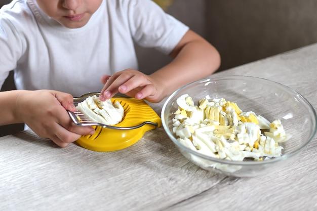 Lifestyle peuter kind meisje koken eten in de keuken. ontwikkeling van fijne motoriek in het dagelijks leven uit afvalmateriaal. het kind snijdt de eieren met een gele eiersnijder.