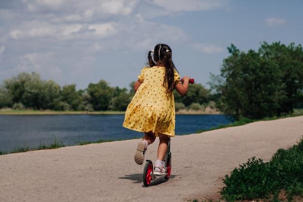 Lifestyle portret achteraanzicht van een meisje in een gele jurk op een scooter op de oever van de rivier in de zomer...