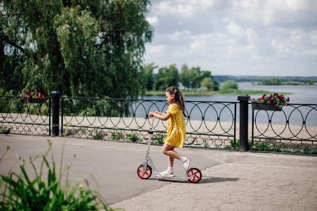 Lifestyle portret een zesjarig meisje in een gele jurk rijdt op een scooter langs de rivier op een zonnige dag...