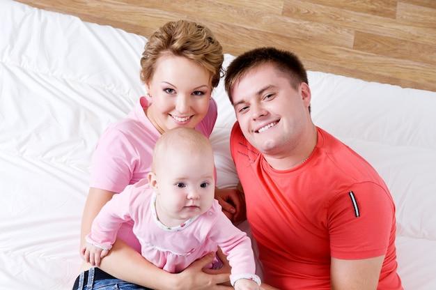 Lifestyle portret van de mooie jonge en gelukkige familie liggend in bed thuis - hoge hoek