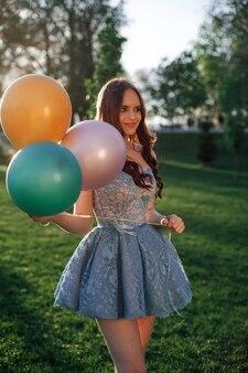 Lifestyle portret van een aantrekkelijke sexy vrouw in een korte blauwe geborduurde jurk met kleurrijke ballo...