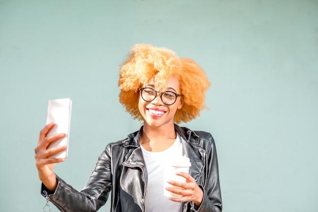 Lifestyle-portret van een afrikaanse vrouw in leren jas die selfie-foto maakt met telefoon op de groene muurachtergrond