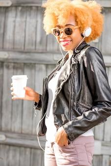 Lifestyle portret van een afrikaanse vrouw in leren jas staande met koffiekopje buiten op de houten muur achtergrond
