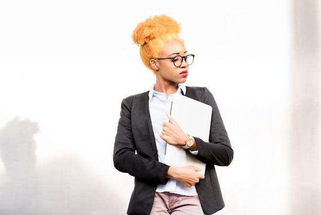 Lifestyle portret van een afrikaanse zakenvrouw in casual pak staande op de grijze muur achtergrond