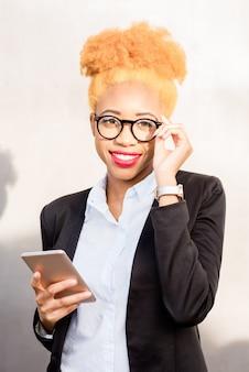Lifestyle-portret van een afrikaanse zakenvrouw in een bril en een casual pak met telefoon op de grijze muurachtergrond