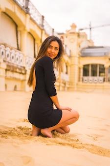 Lifestyle, portret van een jonge brunette blanke vrouw in een korte zwarte jurk, gehurkt in het zand op een strand op zomervakantie