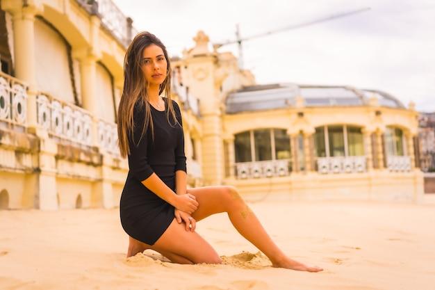 Lifestyle, portret van een jonge brunette blanke vrouw in een korte zwarte jurk, zittend in het zand op een strand op zomervakantie