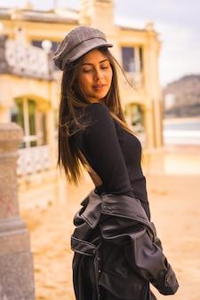 Lifestyle, portret van een jonge brunette blanke vrouw zittend op een trap in een korte zwarte jurk, met een baret en geruite kousen naast een strand, verticale foto