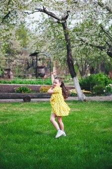 Lifestyle portret van een vrolijk meisje in een gele jurk dansen op het groene gras in een tuin met ...