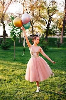 Lifestyle portret van elegante ballerina in een roze zijden jurk en witte pointe-schoenen balancerend op punt...