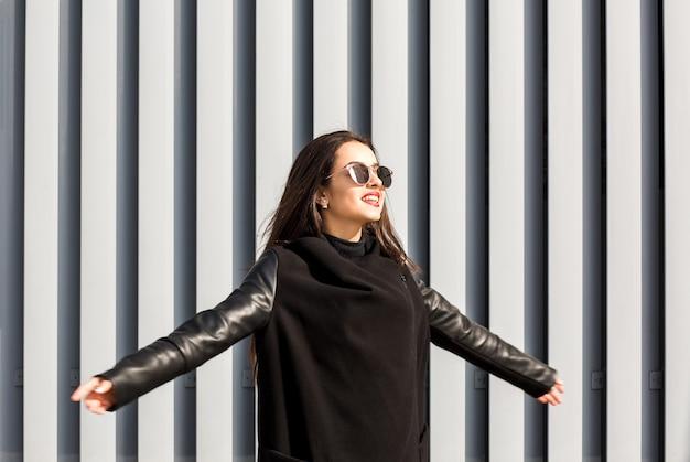 Lifestyle portret van gelukkig jong model met modieuze jas, zonnebril, poseren op straat