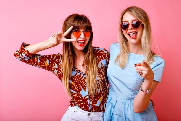 Lifestyle portret van gelukkige mooie twee beste vrienden zus meisjes, poseren en plezier samen op roze muur, met lange tong en v gebaar, positieve feeststemming.
