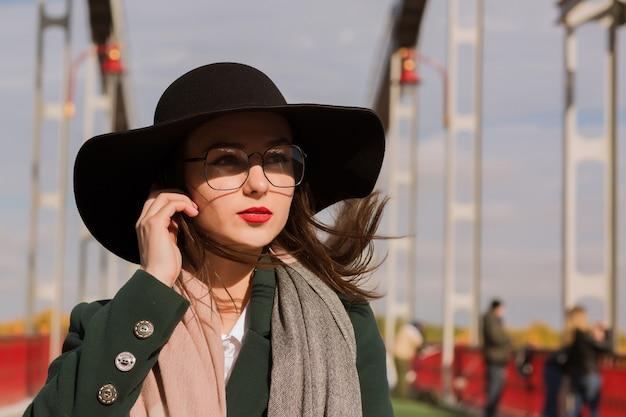 Lifestyle portret van mooie jonge model poseren in zonnige dag. vrouw met modieuze hoed, sjaal en bril