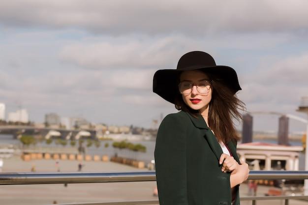 Lifestyle portret van prachtige jonge model poseren in zonnige dag. vrouw met modieuze hoed, sjaal en bril