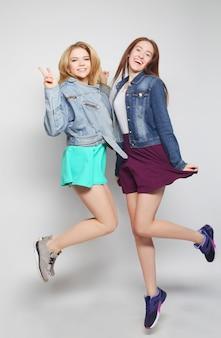 Lifestyle portret van twee jonge hipster meisjes beste vrienden springen over grijze achtergrond