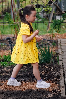 Lifestyle portret van volledige lengte van een meisje in een gele jurk die tussen groentebedden en planten loopt ...