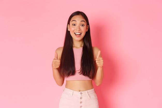 Lifestyle schoonheid en vrouwen concept opgewonden en gelukkig mooi aziatisch meisje dat thumbsup toont en kijkt