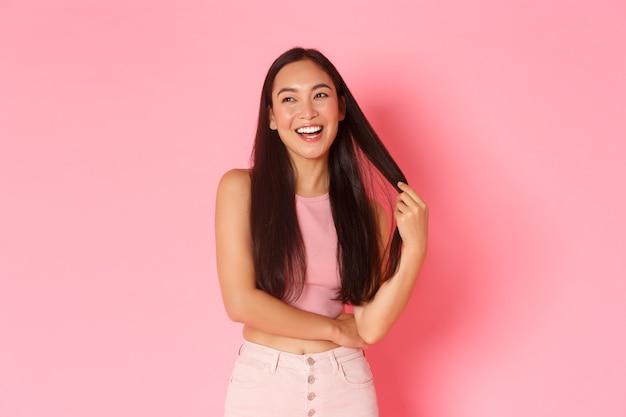 Lifestyle schoonheid en vrouwen concept stijlvol zorgeloos aziatisch meisje dat met haar speelt terwijl ze glimlacht...