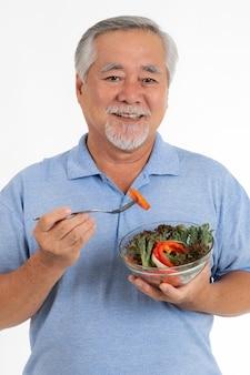 Lifestyle senior man voelt zich gelukkig, geniet van het eten van dieetvoedsel verse salade geïsoleerd op een witte achtergrond
