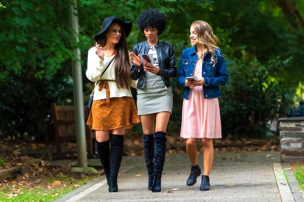 Lifestyle sessie. drie jonge vrienden wandelen in een park, een blonde, een brunette en een latijns meisje