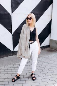 Lifestyle stedelijke mode trendy portret van jonge schattige blondie meisje gekleed in zwart-witte kleding wandelen in de stad in zomerdag in zonnebril