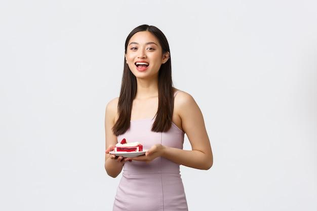 Lifestyle, vakantie, feest en voedselconcept. enthousiast mooi aziatisch meisje dat bij partij eet, die kleding draagt, plaat met stuk cake houdt