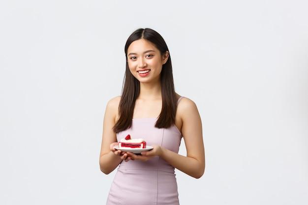 Lifestyle, vakantie, feest en voedselconcept. mooie aziatische vrouw in feestjurk, genietend van het vieren van de verjaardag van een vriend