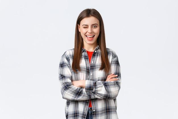 Lifestyle, verschillende emoties, vrijetijdsactiviteiten concept. enthousiaste en zelfverzekerde aantrekkelijke vrouw, vrouwelijke student in geruit casual shirt knipogen opgewonden en glimlachen, kruis armen borst klaar.