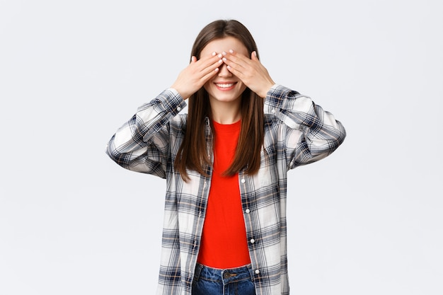 Lifestyle, verschillende emoties, vrijetijdsactiviteiten concept. opgewonden gelukkig jong ontspannen meisje belooft niet te gluren. vrouw bedekt ogen met handpalmen, speelt verstoppertje of wacht op verrassing.
