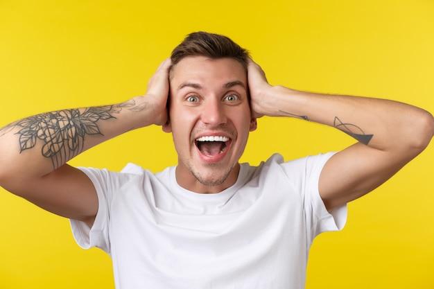 Lifestyle, zomer en mensen emoties concept. close-up portret van een extreem gelukkige, blije jonge man die verrast kijkt, kan niet geloven dat hij de prijs heeft gewonnen, houdt handen op het hoofd in ontkenning, gele achtergrond.