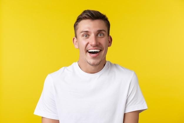 Lifestyle, zomer en mensen emoties concept. close-up van een super blij verraste knappe jongen ontvangt geweldig nieuws, trekt verbaasde wenkbrauwen op en glimlacht, staande gele achtergrond.