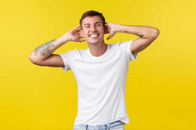 Lifestyle, zomer en mensen emoties concept. zorgeloze knappe gelukkige man met witte vrolijke glimlach, hand in hand achter het hoofd, genietend van vakantie, staande gele achtergrond.