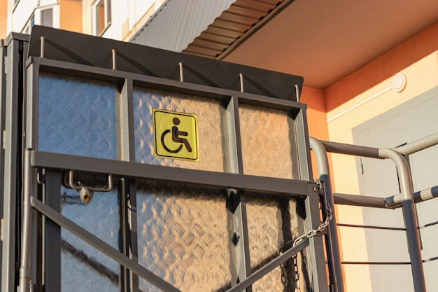 Lift voor mensen met een handicap bij de ingang van een residentieel appartementencomplex. ondersteuning voor mensen die zich in een rolstoel verplaatsen.