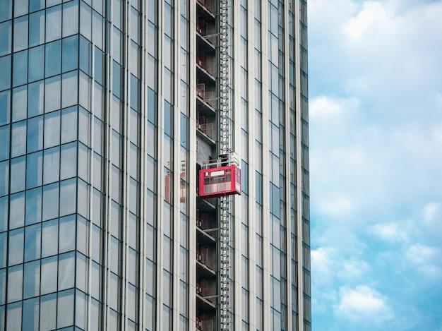Liften liften naar de bouwplaatsen van een wolkenkrabber in aanbouw.