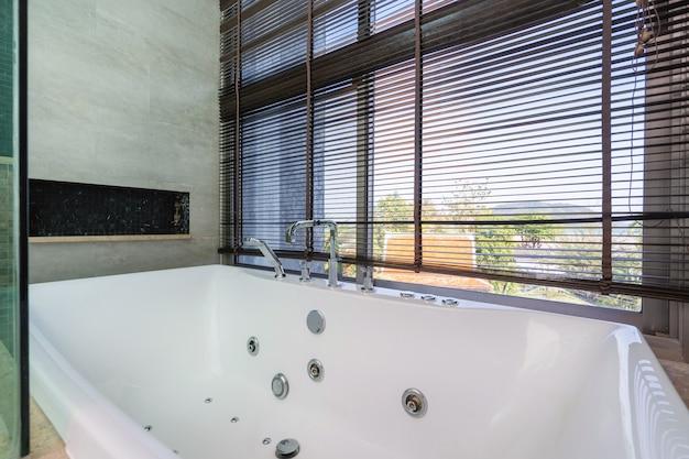 Ligbad en rolgordijn in badkamer van poolvilla, huis, huis, appartement en appartement