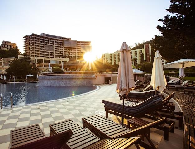 Ligbedden bij het zwembad bij het hotel en zonnestralen. roeping concept. voorbereidingen voor vakantiegangers