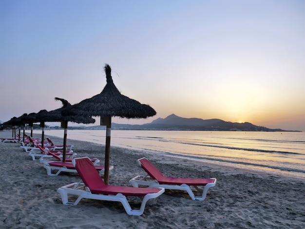 Ligbedden en parasols op zonsopgang alcudia mallorca