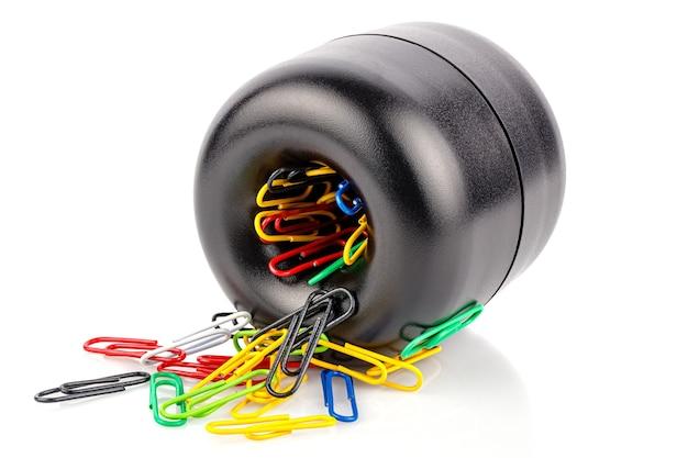 Liggende cilindrische zwarte plastic magnetische houder met gekleurde paperclips geïsoleerd op een witte achtergrond